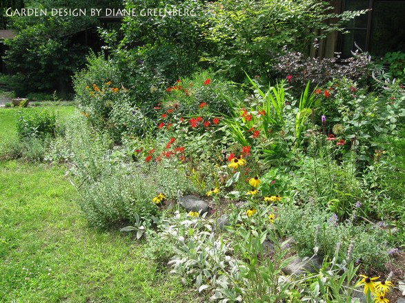 A Semi Fenced, Part Shade Garden With Peony, Iris, Meadow Rue, Baptisia,  Bee Balm, Veronicastrum, And Ferns.
